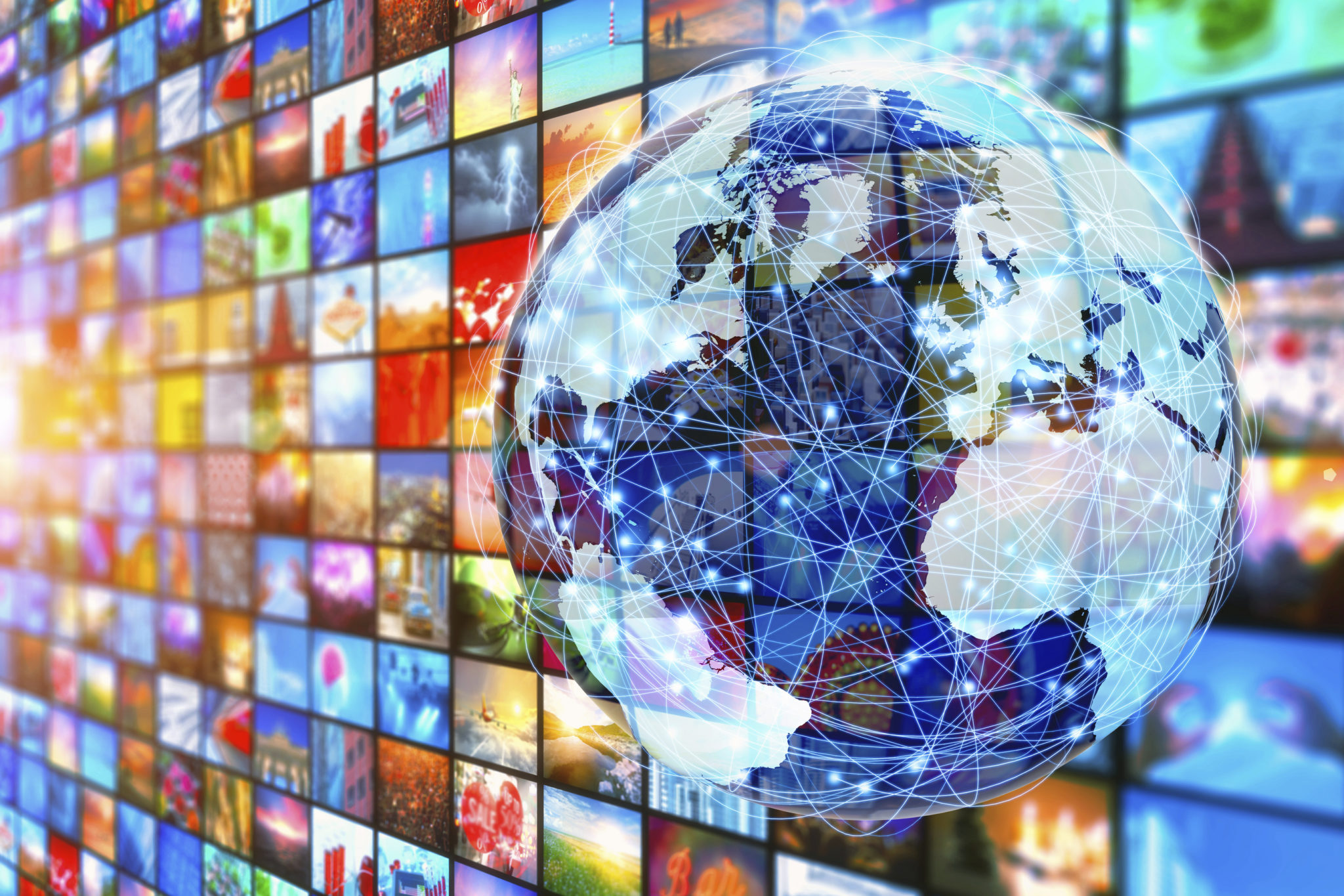 Media wall with a pattern of colorful images resembling a television broadcasting concept with planet Earth in front of it, connected by a global network, with glowing nodes and surrounding links. Hundreds of color video stills projected on television displays around the world, as a metaphor of video entertainment and global communications.